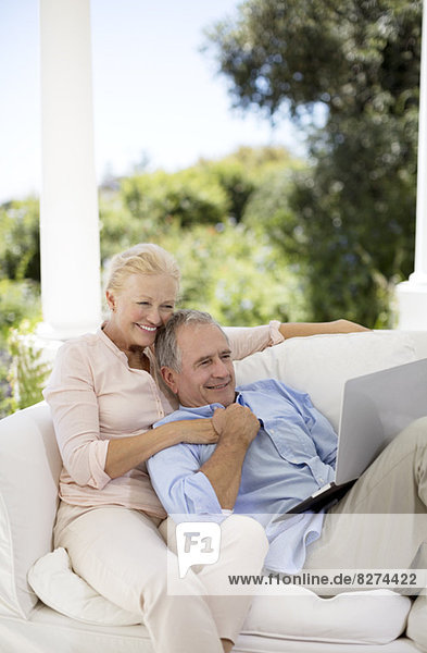 Senior Paar mit Laptop auf der Terrasse Sofa