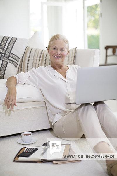 Seniorin mit Laptop auf dem Wohnzimmerboden