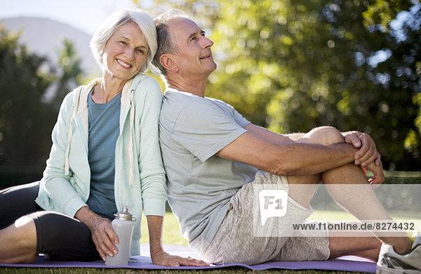 Seniorenpaar sitzend auf Yogamatte im Park