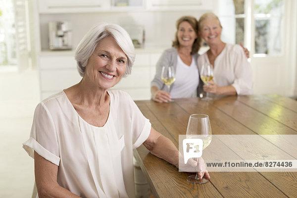 Seniorinnen trinken Weißwein in der Küche
