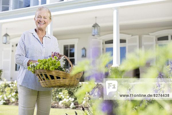 Porträt der Seniorin beim Blumenpflücken im Garten