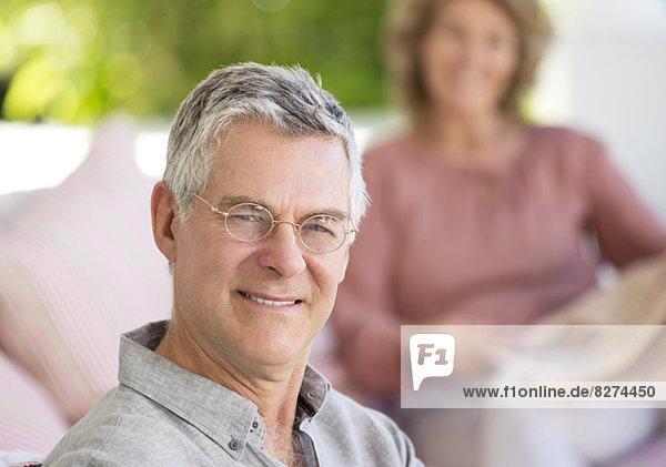 Porträt eines lächelnden älteren Mannes auf der Terrasse