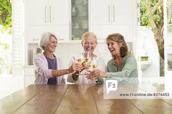 Seniorinnen rösten Weingläser in der Küche.