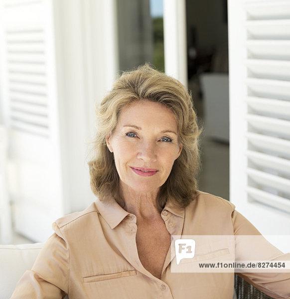 Porträt einer lächelnden Seniorin auf der Terrasse