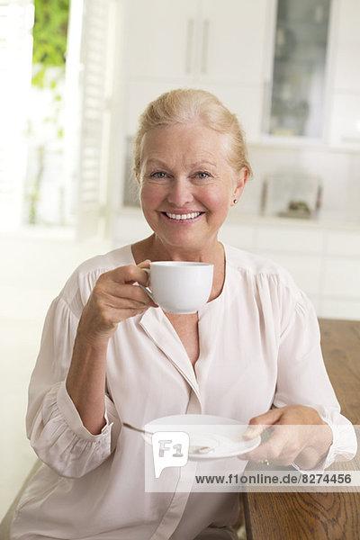 Porträt einer älteren Frau beim Kaffeetrinken