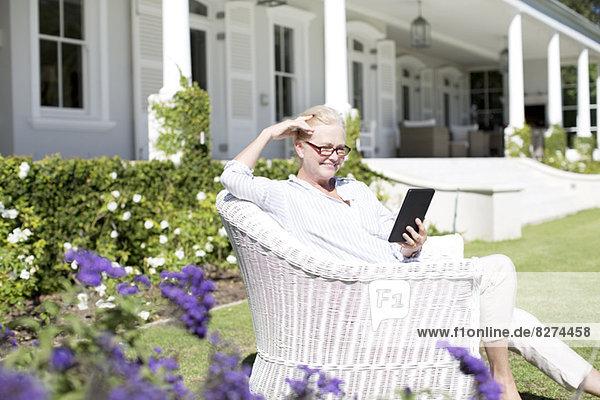 Seniorin mit digitalem Tablett im Garten