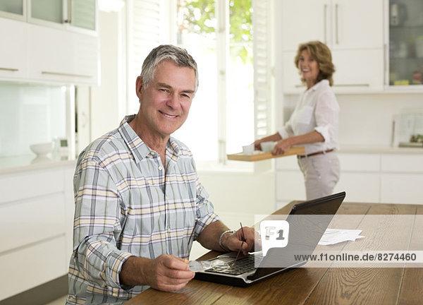 Porträt eines lächelnden älteren Mannes mit Laptop in der Küche