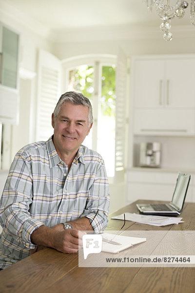 Porträt eines älteren Mannes am Küchentisch