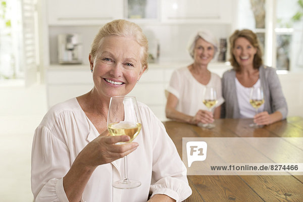 Porträt von lächelnden Seniorinnen beim Weißweintrinken
