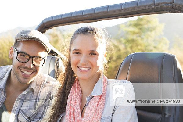 Porträt eines lächelnden Paares im Geländewagen