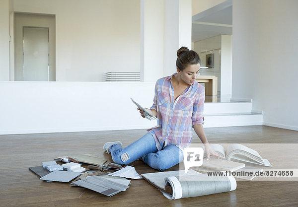 Frau betrachtet Teppich- und Fliesenmuster auf dem Boden im neuen Haus