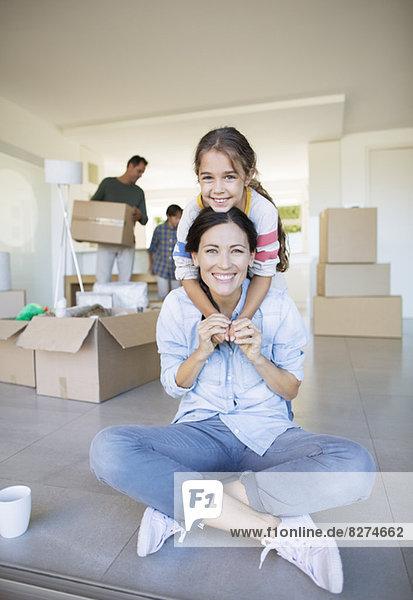 Porträt der lächelnden Mutter und Tochter unter Pappkartons