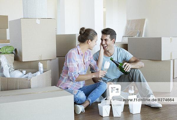 Paar trinkt Champagner und isst chinesisches Essen auf dem Boden im neuen Haus