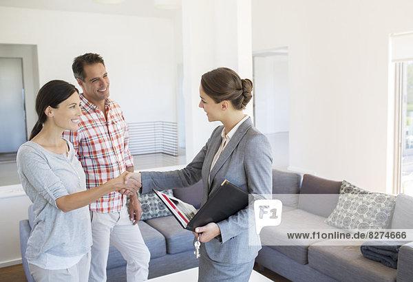 Makler und Ehepaar beim Händeschütteln im Wohnzimmer