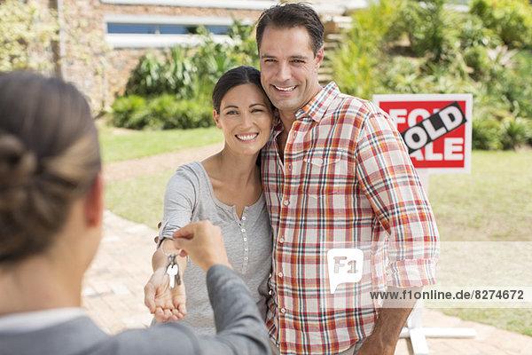 Immobilienmakler gibt Paar Schlüssel zum neuen Haus