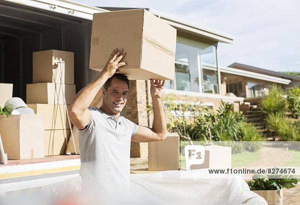 Mann hält Pappkarton oben in der Nähe des fahrenden Vans in der Einfahrt