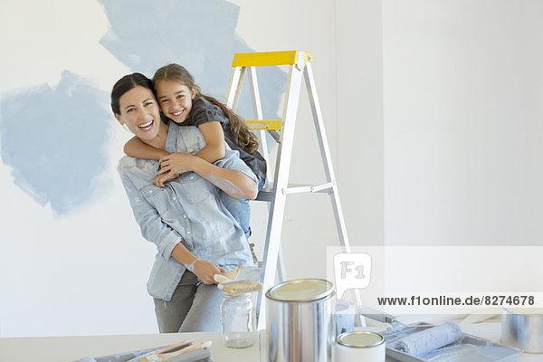 Porträt von Mutter und Tochter beim Umarmen in der Nähe von Farbvorräten