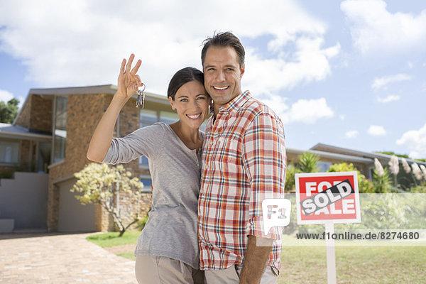 Porträt eines lächelnden Paares mit Schlüsseln vor dem neuen Haus
