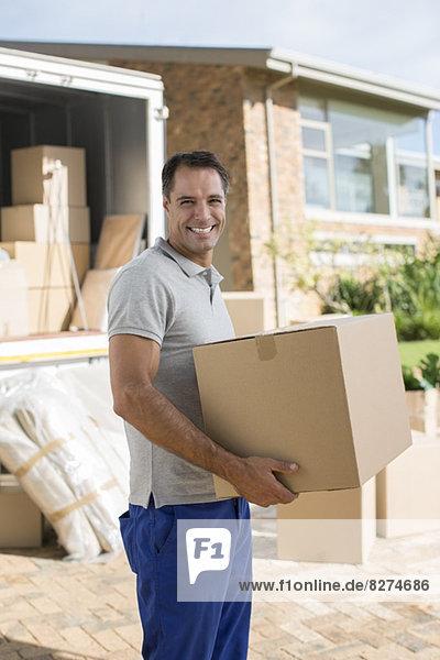 Porträt eines lächelnden Mannes  der einen Karton in der Nähe eines fahrenden Lieferwagens in der Einfahrt hält.