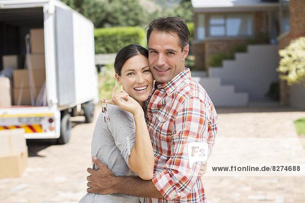 Porträt des lächelnden Paares vor dem neuen Haus