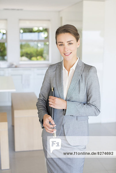Porträt eines selbstbewussten Immobilienmaklers mit Hausschlüssel