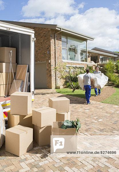 Umzugsunternehmen mit Sofa vom Umzugswagen zum neuen Haus