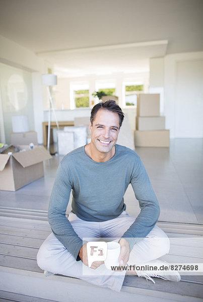 Porträt eines lächelnden Mannes beim Kaffeetrinken zwischen Pappkartons