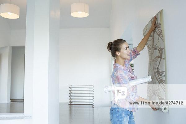 Frau hängend Tapete im neuen Haus