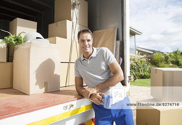 Porträt eines Mannes  der sich auf den Rücken eines fahrenden Vans lehnt.
