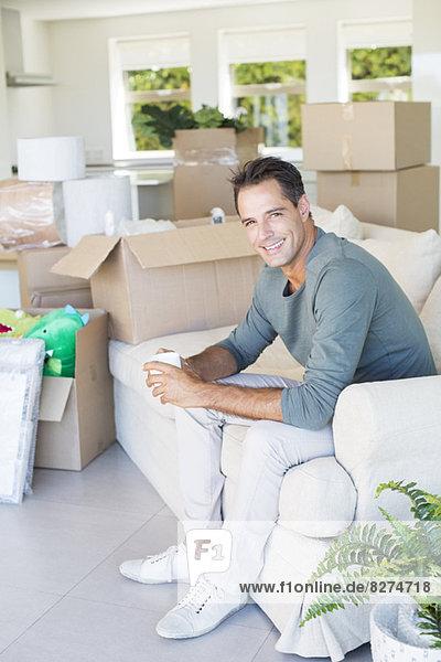 Porträt eines lächelnden Mannes beim Kaffeegenuss auf dem Sofa zwischen Pappkartons