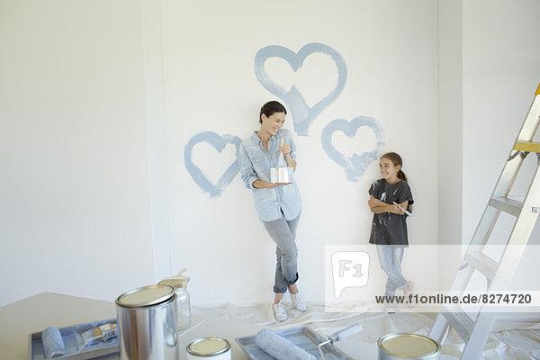 Mutter und Tochter malen blaue Herzen an die Wand