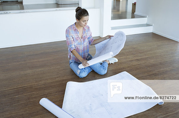 Frau untersucht Blaupausen auf dem Boden im leeren Wohnzimmer