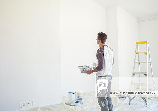 Mann mit Farbwanne mit Blick auf die weiße Wand