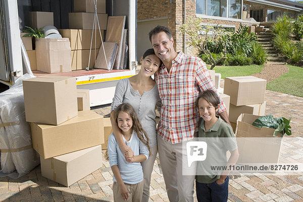 Porträt einer lächelnden Familie in der Nähe eines fahrenden Vans in der Einfahrt