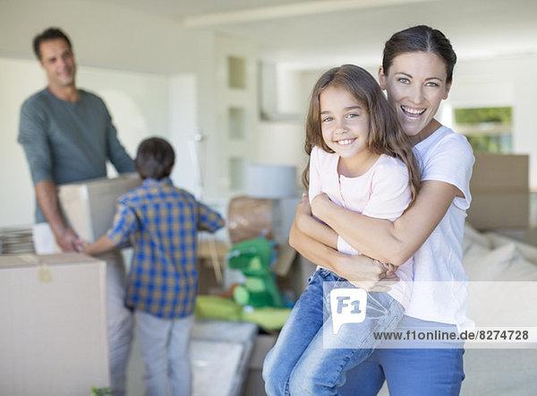 Mutter und Tochter umarmen sich im neuen Haus