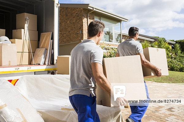 Umzugsunternehmen mit Kisten im neuen Haus