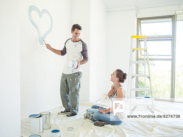 Frau beobachtet Mann malt blaues Herz an der Wand