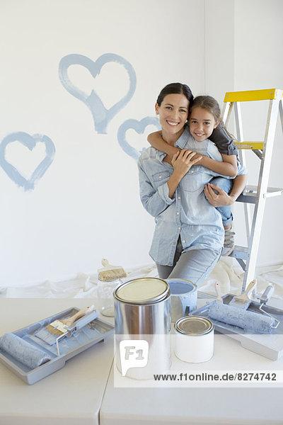 Mutter und Tochter umarmen sich unter den Farbvorräten.