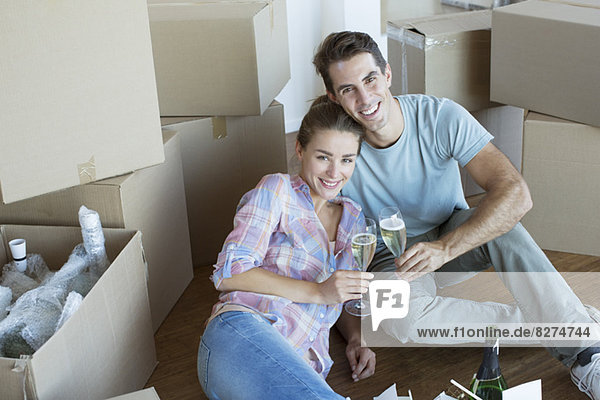 Porträt eines Paares  das Champagner zwischen Pappkartons genießt