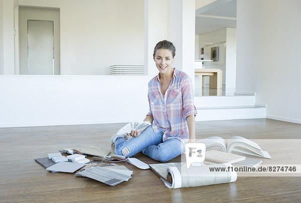 Frau beim Betrachten von Teppichen und Farbmustern im leeren Wohnzimmer