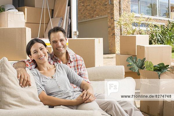 Porträt eines lächelnden Paares auf einem Sofa in der Nähe eines fahrenden Lieferwagens in der Einfahrt.
