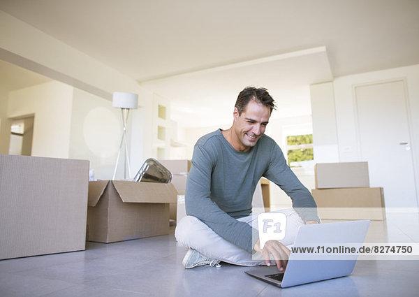 Mann mit Laptop auf dem Boden zwischen Pappkartons