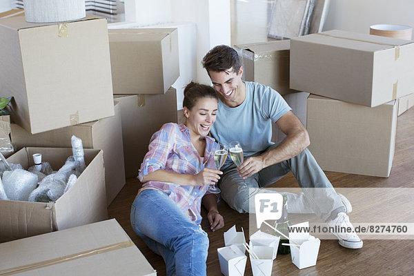 Paar genießt Champagner und Chinesen essen im neuen Haus