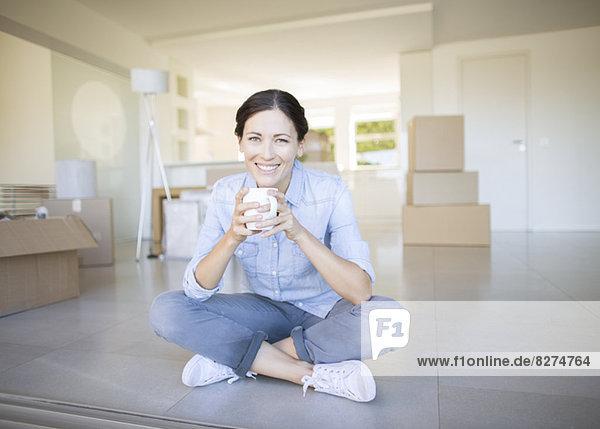 Frau trinkt Kaffee zwischen Pappkartons