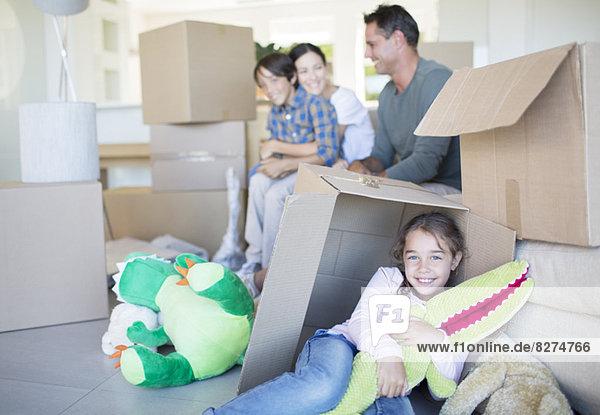 Familie unter den Kartons im Wohnzimmer