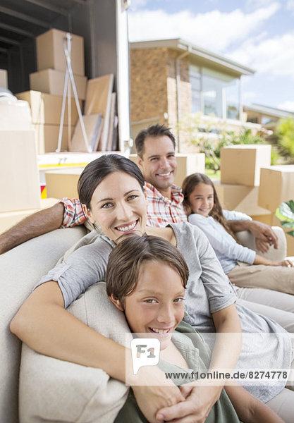Familie sitzend auf Sofa in der Nähe des fahrenden Vans in der Einfahrt