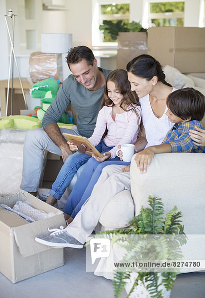 Familie betrachtet Bilderrahmen auf Sofa zwischen Pappkartons