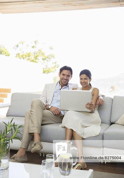 Paar mit Laptop zusammen auf dem Sofa