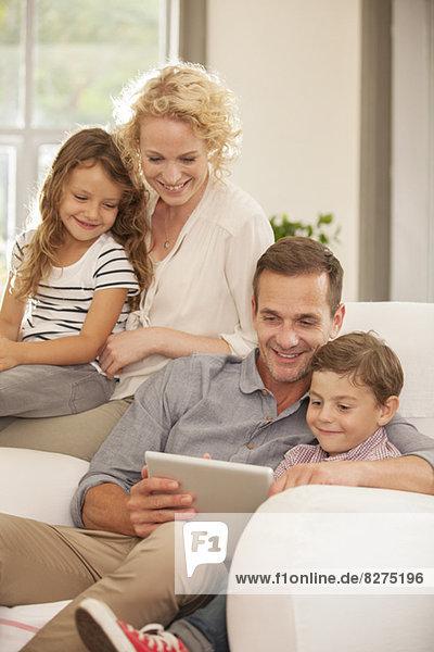 Familie mit digitalem Tablett auf dem Sofa
