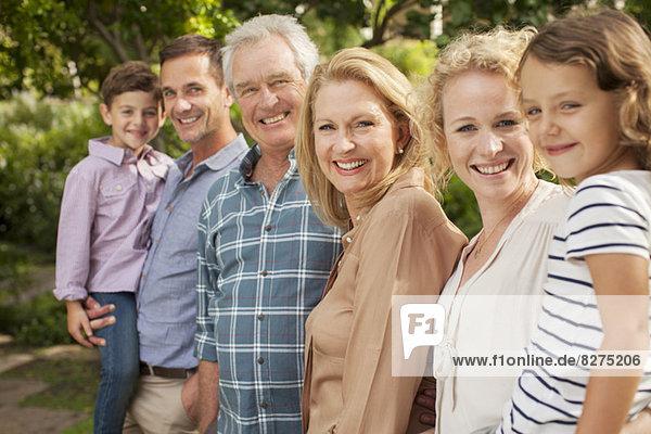 Porträt einer Mehrgenerationen-Familie  die im Freien lächelt